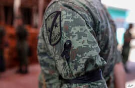 A Mexican army soldier wears a black ribbon on his sleeve during the wake for Alfredo Gonzalez Munoz, a fellow soldier that…