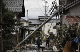 Residents walk along the mud-covered road in a neighborhood devastated by Typhoon Hagibis Tuesday, Oct. 15, 2019, in Nagano,…