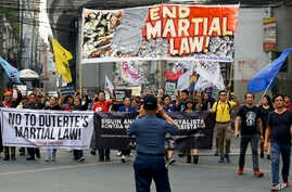 A policeman takes a picture of activists as they march to mark the second year of martial law in Mindanao, during a rally near…