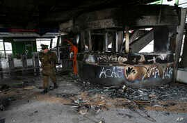 A police officer walks in a subway station that was torched during last night's protests, in Santiago, Chile, Saturday, Oct. 19…