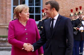 French President Emmanuel Macron welcomes German Chancellor Angela Merkel in the government building of Toulouse, southwestern…