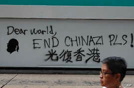 "A man walks past a wall with the words ""Liberate Hong Kong- Dear World End Chinazi Please"" in Hong Kong, Monday, Oct. 7, 2019…"