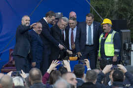 Turkey's President Recep Tayyip Erdogan, center, pushes a button to commence construction of a highway as he stands along with…