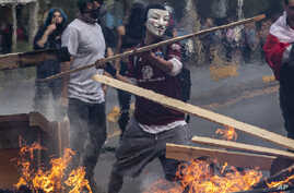 A demonstrator wearing a mask throws a plank of wood into a flaming barricade during a protests in Santiago, Chile, Saturday,…