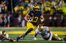 Michigan running back Tru Wilson (13) rushes 27 yards for a touchdown in the fourth quarter of an NCAA college football game…