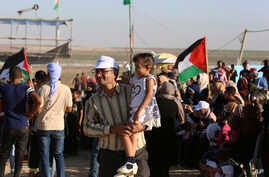 In this Sept. 25, 2019 photo, Palestinian activist Ahmed Abu Artima holds his daughter during an alternative protest he…
