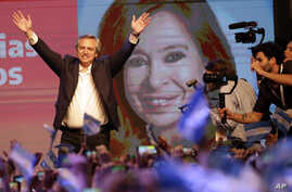 Peronist presidential candidate Alberto Fernández waves to supporters in front of a large image of his running mate, former…