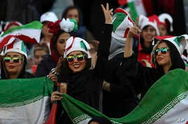 An Iranian women flashes a victory sign during a soccer match between Iran and Cambodia in the 2022 World Cup qualifier, at the…
