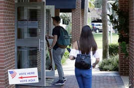 In this  Wednesday, Oct. 31, 2018 photo, students enter a polling place to cast their ballots during a Vote for Our Lives event…