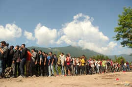 FILE - In this file photo dated Wednesday, June 19, 2019, migrants and refugees wait in line to receive supplies from the Red…