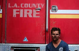 Los Angeles County Firefighter Collin Bashara takes rest with his fire truck in Los Angeles, Monday, Oct. 28, 2019. (AP Photo…
