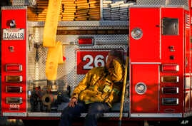 A firefighter leans against his fire truck while resting from working on a wildfire in Los Angeles, Monday, Oct. 28, 2019. (AP…