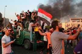 Anti-government protesters take over an armored vehicle before they burn it during a demonstration in Baghdad, Thursday,…