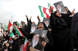 Demonstrators cry and pray as they hold up portraits of Supreme Leader Ayatollah Ali Khamenei at a pro-government rally…