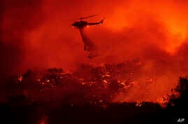 A helicopter drops water on the Cave Fire burning along Highway 154 in Los Padres National Forest, Calif., above Santa Barbara…