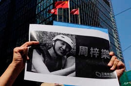 A protester holds a photo of Chow Tsz-Lok during a memorial flash mob to remember him near Chinese and Hong Kong flags in Hong…