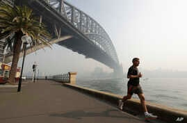 A man jogs under the Sydney Harbour Bridge as a smoke haze hangs over Sydney, Thursday, Nov. 21, 2019. The annual Australian…