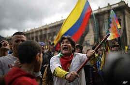 An anti-government protester chants during a demonstration in Bogota, Colombia, Wednesday, Nov. 27, 2019. Colombians unhappy…