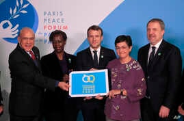 French President Emmanuel Macron, center, OECD secretary general Angel Gurria, left, ,and other U.N officers hold a placard as…