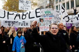 A woman raises her fist as she protests against domestic violence, in Paris, Saturday, Nov, 23, 2019. Protesters are marching…