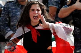 An anti-government school student shouts slogans, during ongoing protests against the Lebanese government in front the…