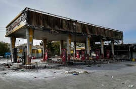 This photo released by the Iranian Students' News Agency, ISNA, shows a gas station that was burned during protests that…