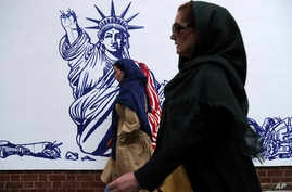 People walk past a satirical drawing of Statue of Liberty after new anti-U.S. murals on the walls of former U.S. embassy…