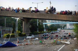 Protestors stand on a barricaded bridge as traffic makes its way underneath near the Chinese University of Hong Kong in Hong…