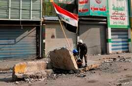 Anti-government protesters take cover during clashes with security forces on Rasheed Street, Baghdad, Iraq, Tuesday, Nov. 26,…