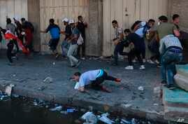 Anti-government protesters run for cover in Iraq