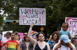 Transgender and non-binary individuals and their allies stroll through the city's Midtown district during Gay Pride's…