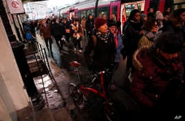 Commuters walk to get on a train at the Gare Saint Lazare station in Paris, France, Monday, Dec. 16, 2019. French transport…
