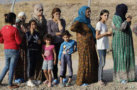 Syrian women who were displaced by the Turkish military operation in northeastern Syria line up to receive aid and food…