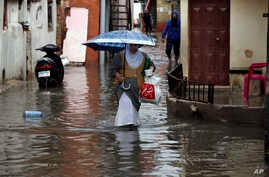 People walk through floodwaters in Beirut's southern suburb of Ouzai, Lebanon, Monday, Dec. 9, 2019. A rainstorm paralyzed…