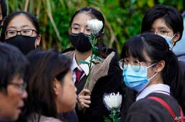 Mourners line up for a memorial service to pay their respects to Chow Tsz-lok, a student who died after falling off a parking…