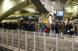 Commuters leave a train at the Montparnasse train station, Paris, France