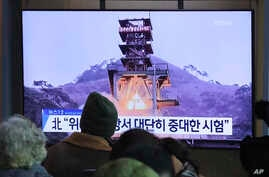 People watch a TV screen showing a file image of a ground test of North Korea's rocket engine during a news program at the…