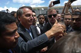 Brazil's President Jair Bolsonaro flashes a thumbs up as he greets supporters after attending a Changing of the Guard at the…