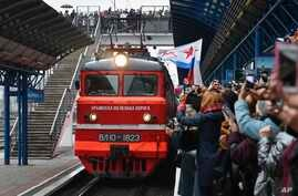 People celebrate the arrival of the train from Russia in Sevastopol, Crimea, after it crossed a bridge linking Russia and the…