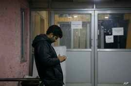 A man checks his cellphone outside a media facilitation centre in Srinagar, Indian controlled Kashmir, Tuesday, Dec. 31, 2019…