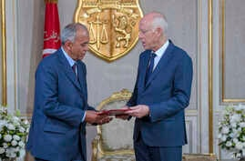 In this photo provided by the Tunisian Presidency, Tunisian President Kais Saied, right, speaks with Tunisia's new Prime…