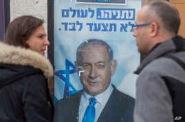 People look at a poster of Israel Prime Minister and governing Likud party leader Benjamin Netanyahu at a voting center in the…