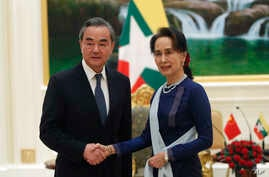Myanmar's leader Aung San Suu Kyi, right, shakes hands with Chinese Foreign Minister Wang Yi, left, during their meeting at the…