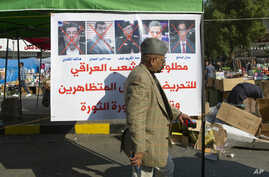 "A protester walks past a poster with defaced pictures of Iraqi politicians and Arabic that reads ""wanted by the Iraqi people…"