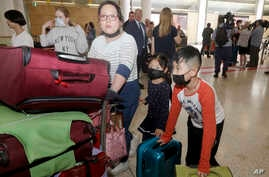 A woman and her children, wearing face masks, arrive in Sydney Thursday, Jan. 23, 2020, from a flight from Wuhan, China. China…