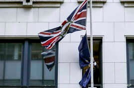 A member of protocol removes the European Union flag from the UK Permanent Representation to the EU in Brussels, Friday, Jan…