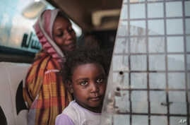FILE - In this file picture taken Tuesday, April 14, 2015, a Sudanese girl looks out of the window while waiting with her…