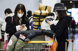 Travelers from Beijing, wearing masks, use their cellphone as they arrive at Charles de Gaulle airport, north of Paris, early…