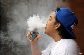 A man, who declined to be identified, puffs out a vapor cloud while smoking an electronic cigarette during a work break…
