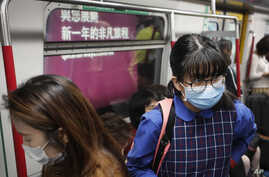 Commuters wear protection masks inside a subway train in Hong Kong, Tuesday, Jan. 7, 2020. Hong Kong health chief Sophia Chan…